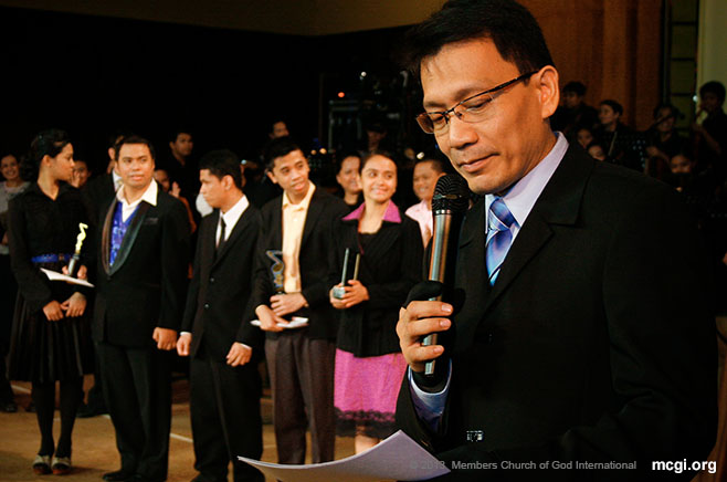 ASOP Music Festival's co-progenitor, Bro. Daniel Razon, holding the results of the Mid-Year Festival last year. MCGI's songwriting event was launched in 2004.
