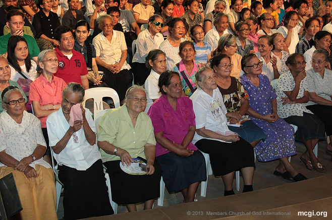In one of MCGI's Thanksgiving services, widows sit in front of the ADD Convention Center stage.