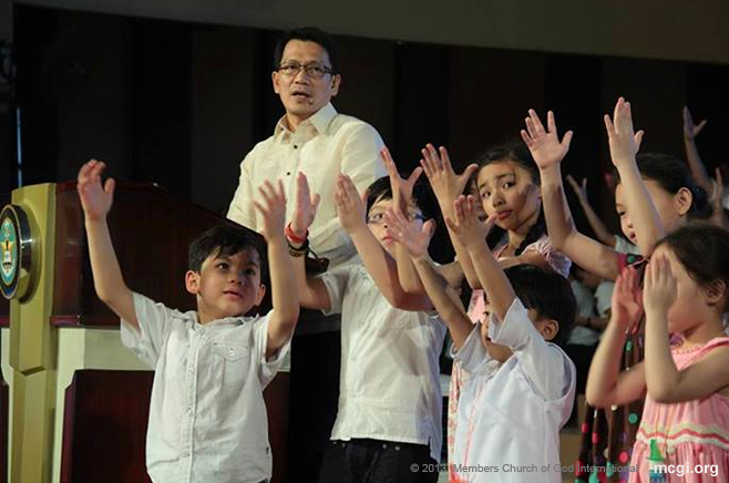 Bro. Daniel Razon, MCGI Vice Presiding Minister is joined by his children and family onstage in offering thanksgiving to the Lord in September 2013.