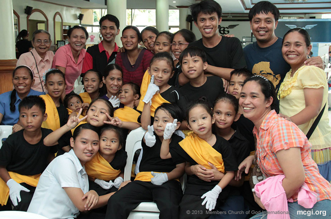 At the ADD Convention Center, parents and children pose and smile together after a Kawan ng Cordero (KNC) presentation in one of MCGI's Thanksgiving services.