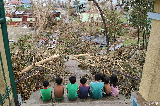 Children sit by the entrance of the Hagnaya Elementary School in San Remegio, Cebu after Typhoon Haiyan (Yolanda) devastates their town.