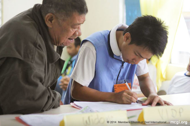 A volunteer Lingap Kapatid member (Brethren Welfare) assists an elderly in signing his name in the Transient Home. (Courtesy of PVI)