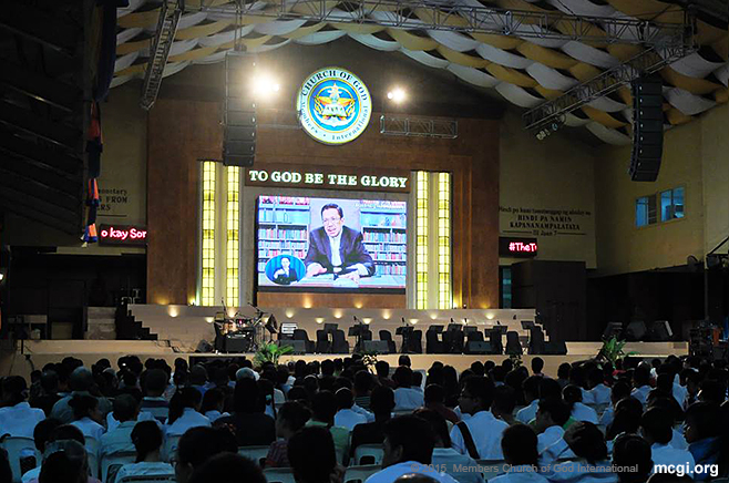 Through satellite technology, Bro. Eli Soriano can talk with people from different points worldwide and read the Bible's answers to their questions live . (Photo courtesy of Photoville International)