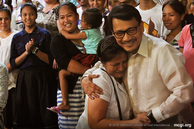 One of the thousand newly-baptized brethren from this year, Sis Amelia Acebuche is overcome with emotion as Bro. Daniel Razon, Assistant Over-all Servant of MCGI, takes a picture with her during her testimony. (Photo courtesy of Photoville International)